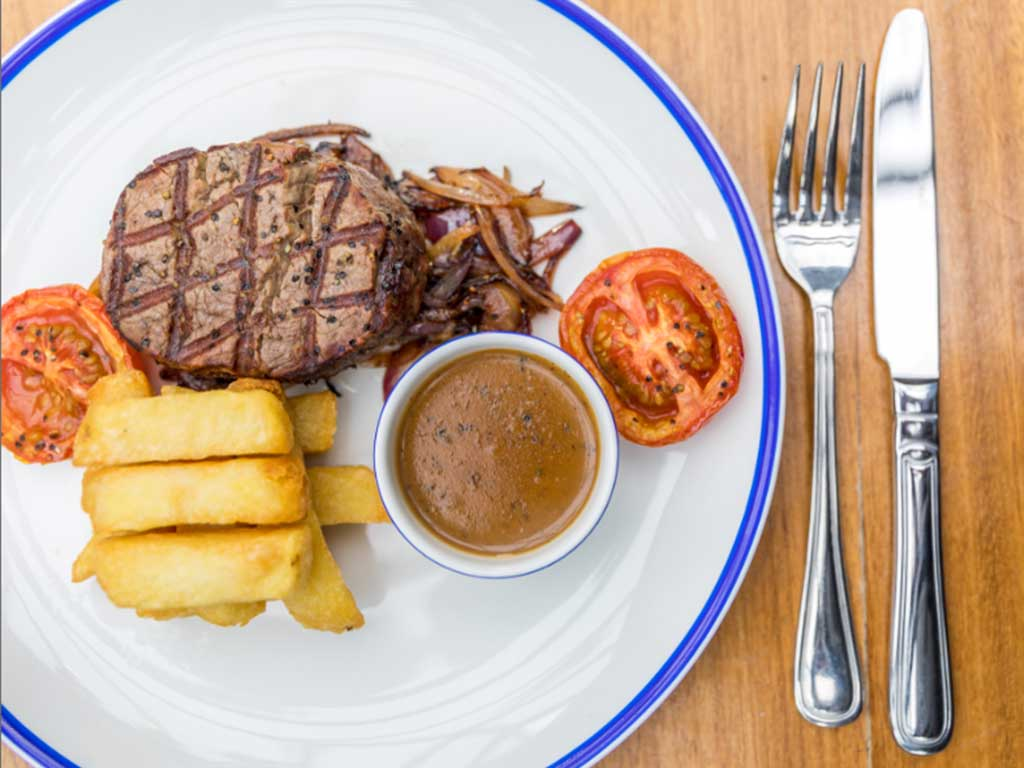 Steak with pepper sauce, tomato and chips